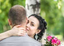 Portrait of pretty young female with small pink roses bouquet smiling, gently hugging male neck and looking into camera at sunny s. Ummer park. Romance and love Royalty Free Stock Photos