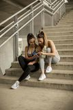 Young females runner resting on stairs. Portrait of pretty young females runner resting on stairs Royalty Free Stock Image