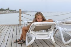 Portrait of pretty young gill looking at camera lying on sun lounger stock image