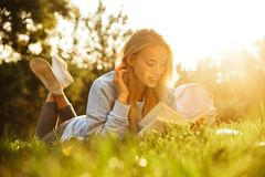 Portrait of a pretty young girl with backpack. Laying on a grass at the park, reading a book Stock Photo