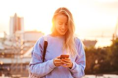 Portrait of a pretty young girl with backpack. Standing outdoors during sunset, holding mobile phone Royalty Free Stock Photography