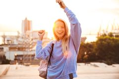 Portrait of a pretty young girl with backpack. Standing outdoors during sunset, holding mobile phone, celebrating Royalty Free Stock Images