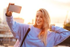 Portrait of a pretty young girl with backpack. Standing outdoors during sunset, taking selfie with mobile phone Stock Images