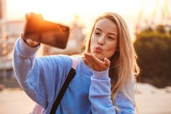 Portrait of a pretty young girl with backpack standing. Outdoors during sunset, taking selfie with mobile phone, sending kiss Royalty Free Stock Image