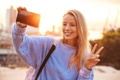 Portrait of a pretty young girl with backpack standing. Outdoors during sunset, taking selfie with mobile phone, showing peace Royalty Free Stock Photos