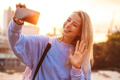 Portrait of a pretty young girl with backpack. Standing outdoors during sunset, taking selfie with mobile phone, waving Royalty Free Stock Photo