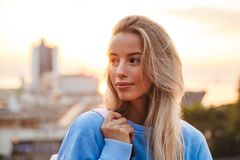 Portrait of a pretty young girl with backpack standing. Outdoors during sunset Stock Image