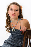 Portrait of a pretty young girl with clean skin. Girl with long curly hairs. She sit on old chair Stock Photo