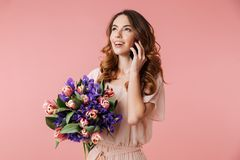 Portrait of a pretty young girl in dress. Talking on mobile phone while holding big bouquet of irises and tulips isolated over pink background Stock Photo