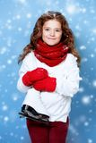 Skating time in winter. A portrait of a pretty young girl holding skates. Winter fashion for kids, beauty, active and healthy lifestyle stock photo