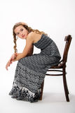 Portrait of a pretty young girl with long hair. Portrait of a pretty young girl with long curly hairs. She sit on old chair Stock Photography