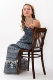 Portrait of a pretty young girl with long hair. Portrait of a pretty young girl with long curly hairs. Girl sit on old chair Stock Photography