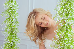 Portrait of a pretty young girl looks to flowers. Portrait of a pretty young girl looks to the flowers Stock Image