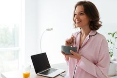 Portrait of a pretty young girl in pajamas having a breakfast. At the kitchen with blank screen laptop computer on a table Stock Images