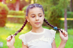 Portrait of pretty young girl with pigtails at sunny day Stock Photo