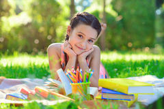 Portrait of pretty young girl reading book in park Royalty Free Stock Photography