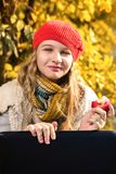 Portrait of pretty young girl in red hat eating an apple and smiling royalty free stock photography
