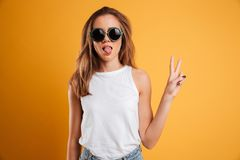 Portrait of a pretty young girl showing peace gesture. Portrait of a pretty young girl in sunglasses showing peace gesture and looking at camera isolated over Stock Photography