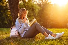 Portrait of a pretty young girl sitting on a grass. At the park, reading a book, taking notes Stock Photos