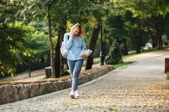 Portrait of a pretty young girl student with backpack. And textbook walking at the park, talking on mobile phone Stock Photos