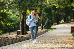 Portrait of a pretty young girl student with backpack. And textbook walking at the park, holding mobile phone Stock Photos