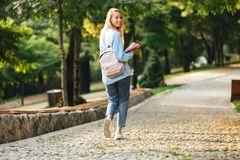 Portrait of a pretty young girl student with backpack. And textbook walking at the park Royalty Free Stock Photo