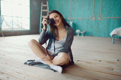 Portrait of pretty young girl taking picture on film camera Stock Photography