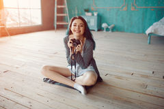 Portrait of pretty young girl taking picture on film camera Royalty Free Stock Image