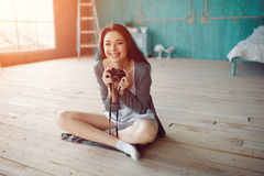 Portrait of pretty young girl taking picture on film camera Stock Image