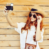 Portrait of pretty young girl taking selfies with old camera Royalty Free Stock Image