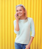 Portrait of pretty young girl talking on the smartphone. Near a colorful yellow wall Stock Image