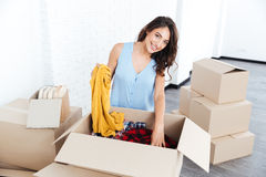 Portrait of a pretty young girl unpacking in new flat Royalty Free Stock Photography