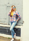 Portrait pretty young girl wearing a checkered shirt and sunglasses Royalty Free Stock Image