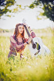 Portrait of pretty young hippie girl with guitar. Outdoor shot Royalty Free Stock Images