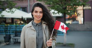 Portrait of pretty young lady holding Canadian flag in the street smiling. Portrait of pretty young lady patriot holding Canadian flag in the street smiling stock footage