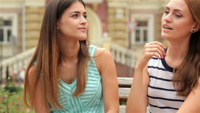 Portrait of pretty young laughing girlfriends. Two beautiful young woman resting on a bench after shopping stock footage