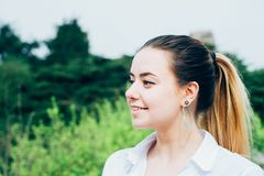 a pretty young woman in white shirt, smiling, heart shaped earing stock images