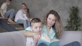 Portrait of pretty young mother reading book to her son while the rest of her teen kids playing with each other in the stock video