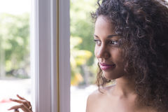 Portrait of pretty young mulatto woman looking at window. She is happy Stock Photos