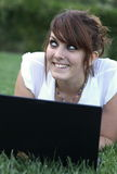 Portrait of a pretty young woman. Smiling while working on a laptop outdoors Royalty Free Stock Images