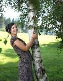 Portrait of a pretty young woman. Posing by a birch smiling and looking at the camera Royalty Free Stock Images