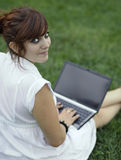 Portrait of a pretty young woman. Smiling while working on a laptop outdoors Stock Photos