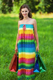 Portrait pretty young woman. Standing keeps shoulders shopping bags background summer green park Stock Photography