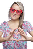 Portrait of a pretty young woman. With heart-shape sunglasses making heart sign over her heart on white background Royalty Free Stock Photography