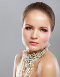Portrait of pretty young woman with beads and Stock Photos