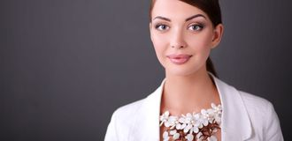Portrait of young woman with beads, standing on gray background Royalty Free Stock Photos
