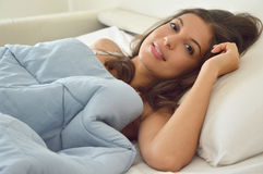 Portrait pretty young woman on bed looking at camera in modern apartment in the morning. Portrait pretty young woman on bed looking at camera in modern Stock Photo