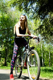 Portrait of pretty young woman with bicycle in a park - outdoor Royalty Free Stock Image