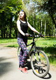 Portrait of pretty young woman with bicycle in a park - outdoor Stock Photos