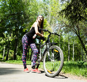 Portrait of pretty young woman with bicycle in a park - outdoor Stock Images